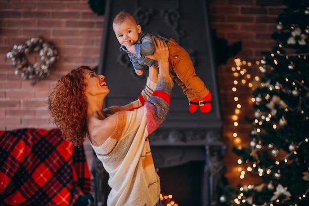 Mutter mit ihrem kleinen sohn am weihnachtsbaum Kostenlose Fotos