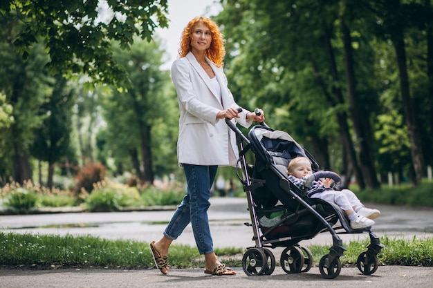 Mutter mit ihrem kleinen sohn in einem kinderwagen im park Kostenlose Fotos