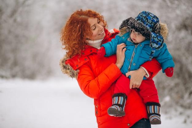 Mutter mit ihrem kleinen sohn zusammen in einem winterpark Kostenlose Fotos