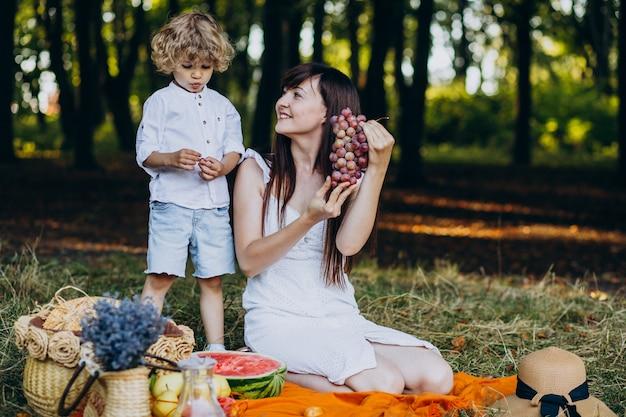 Mutter mit ihrem sohn beim picknick im wald Kostenlose Fotos