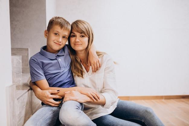 Mutter mit ihrem sohn zusammen auf dem boden sitzen Kostenlose Fotos