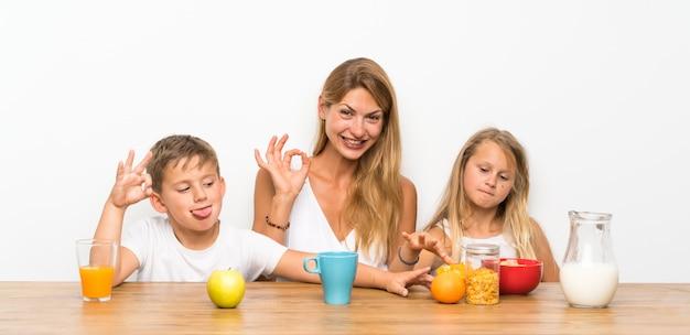 Mutter mit ihren zwei kindern, die frühstücken und okayzeichen bilden Premium Fotos