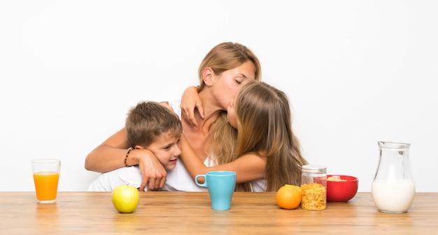 Mutter mit ihren zwei kindern, die frühstücken und umarmen Premium Fotos