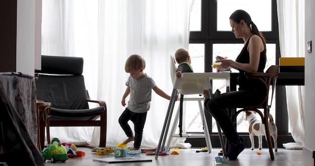 Mutter mit ihren zwei kindern, die zu hause sitzen. ein elternteil füttert ein kind in einem hochstuhl. Premium Fotos