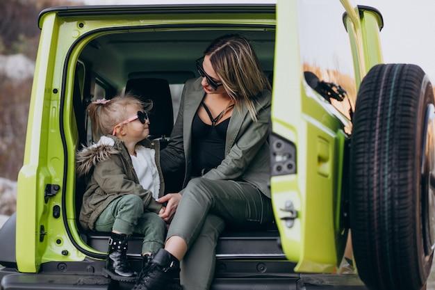 Mutter mit ihrer kleinen tochter, die hinten im auto sitzt Kostenlose Fotos