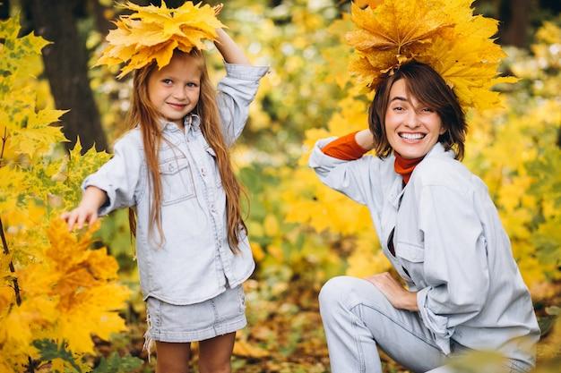 Mutter mit ihrer kleinen tochter im wald voller goldener blätter Kostenlose Fotos