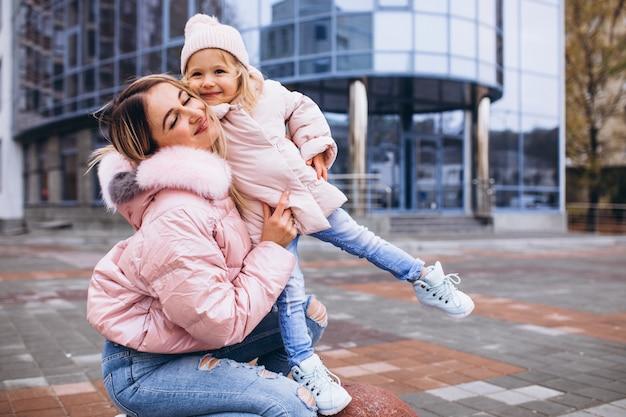 Mutter mit ihrer kleinen tochter in warmem tuch am straßenrand Kostenlose Fotos