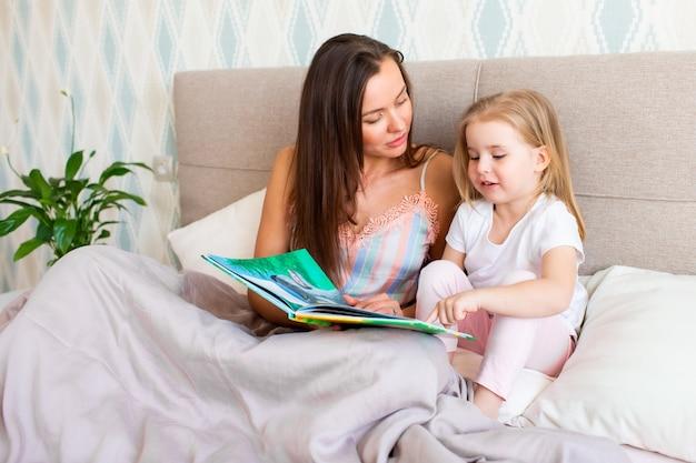 Mutter mit ihrer tochter liest ein buch Premium Fotos