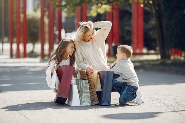 Mutter mit kind mit einkaufstasche in einer stadt Kostenlose Fotos
