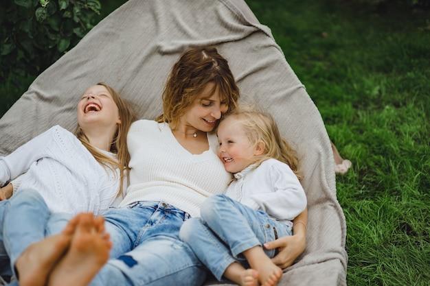 Mutter mit kindern, die spaß in einer hängematte haben. mutter und kinder in einer hängematte. Kostenlose Fotos