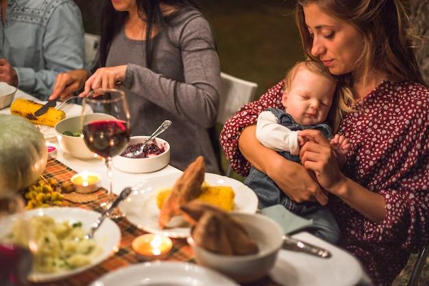 Mutter mit kleinem baby am familienabendessen Kostenlose Fotos