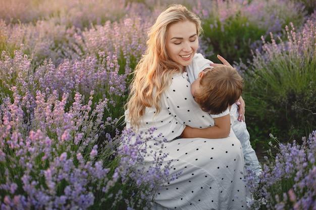 Mutter mit kleinem sohn auf lavendelfeld. schöne frau und niedliches baby, das im wiesenfeld spielt. familienurlaub im sommertag. Kostenlose Fotos