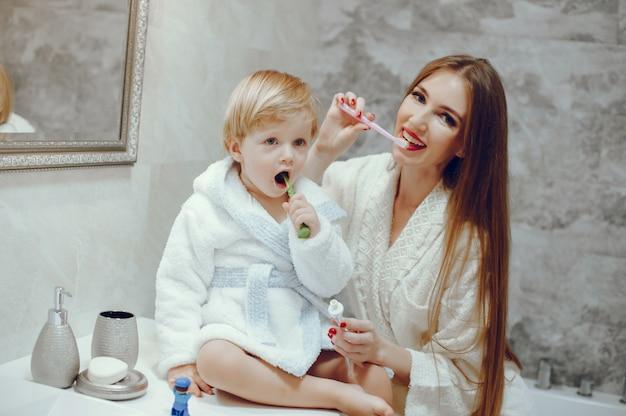 Mutter mit kleinem sohn in einem badezimmer Kostenlose Fotos