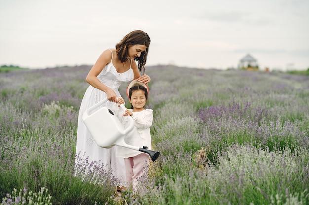 Mutter mit kleiner tochter auf lavendelfeld. schöne frau und niedliches baby, das im wiesenfeld spielt. familienurlaub im sommertag. Kostenlose Fotos