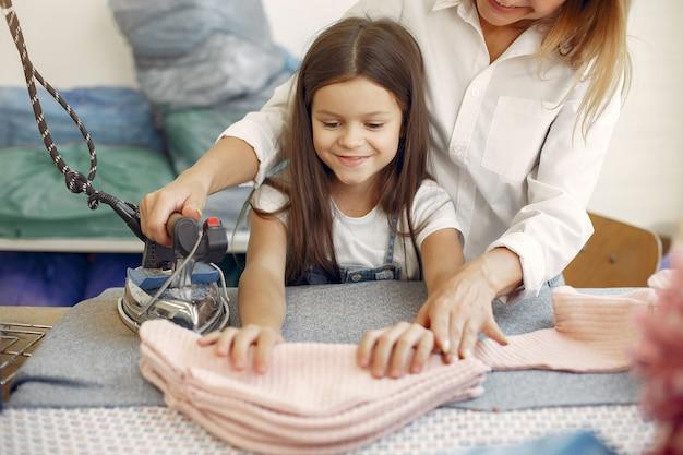 Mutter mit kleiner tochter bügeln den stoff in der fabrik Kostenlose Fotos