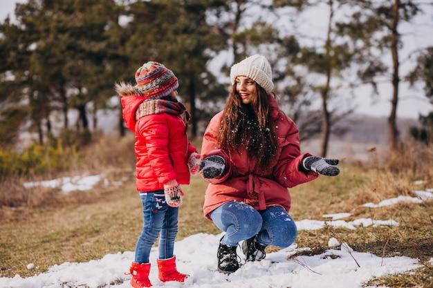 Mutter mit kleiner tochter in einem winterwald Kostenlose Fotos
