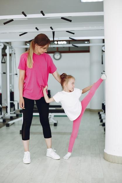Mutter mit kleiner tochter nehmen an gymnastik in der turnhalle teil Kostenlose Fotos