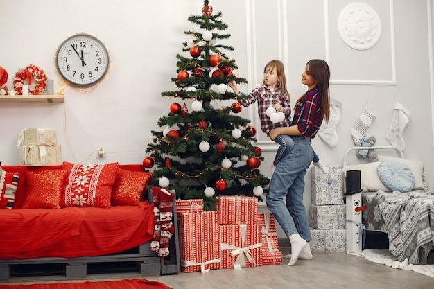 Mutter mit netter tochter zu hause mit weihnachtsgeschenken Kostenlose Fotos