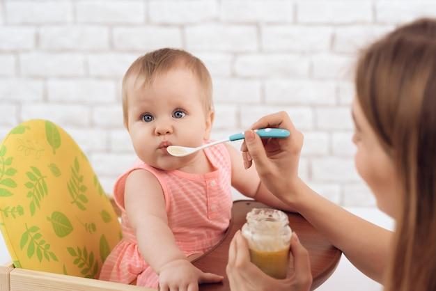 Mutter mit püree und löffel füttert kleines baby Premium Fotos