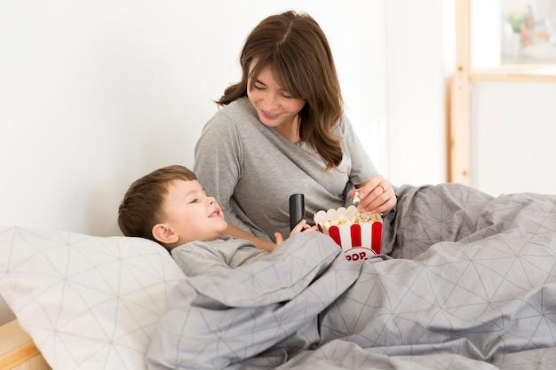 Mutter mit sohn im bett popcorn essend | Kostenlose Foto