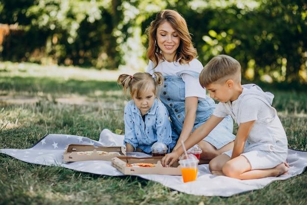 Mutter mit sohn und tochter essen pizza im park Kostenlose Fotos