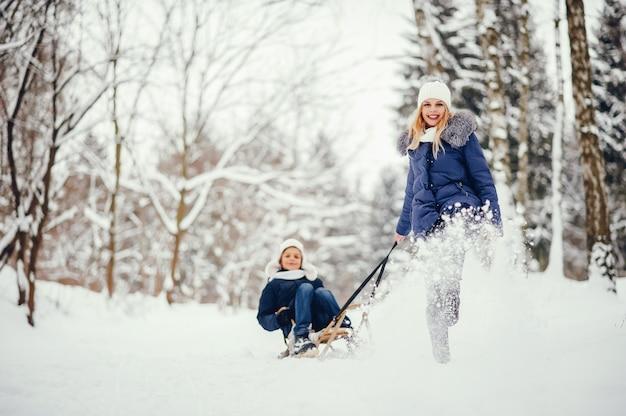 Mutter mit süßen sohn in einem winter oark Kostenlose Fotos