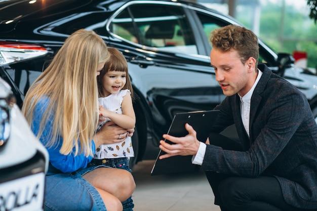Mutter mit tochter im gespräch mit verkäufer in einem autosalon Kostenlose Fotos