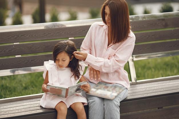 Mutter mit tochter liest ein buch in der stadt Kostenlose Fotos