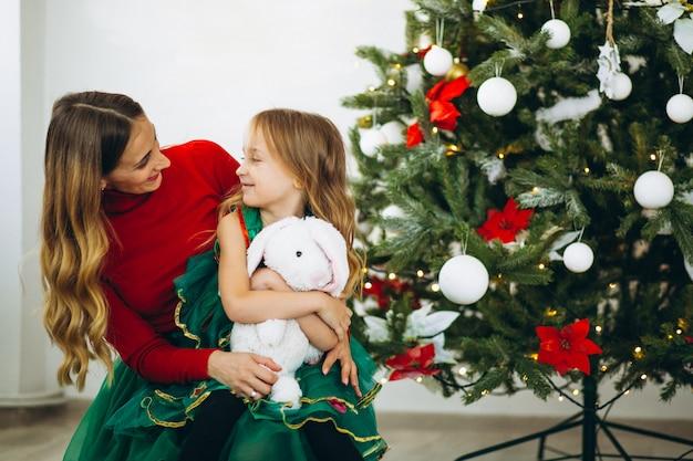 Mutter mit tochterverpackungsgeschenken durch weihnachtsbaum Kostenlose Fotos