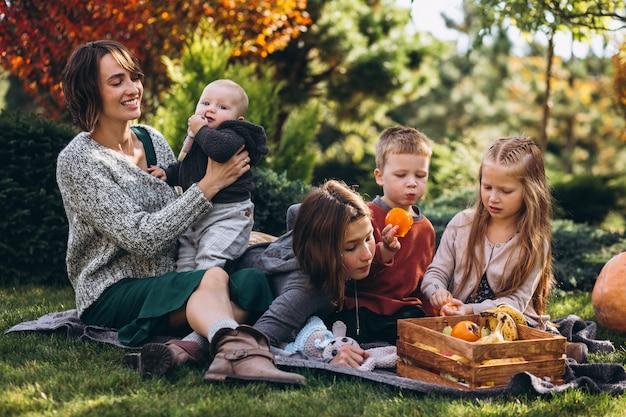 Mutter mit vier kindern, die picknick auf hinterhof haben Kostenlose Fotos