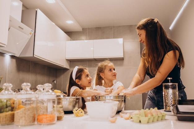 Mutter mit zwei töchtern beim küchenbacken Kostenlose Fotos