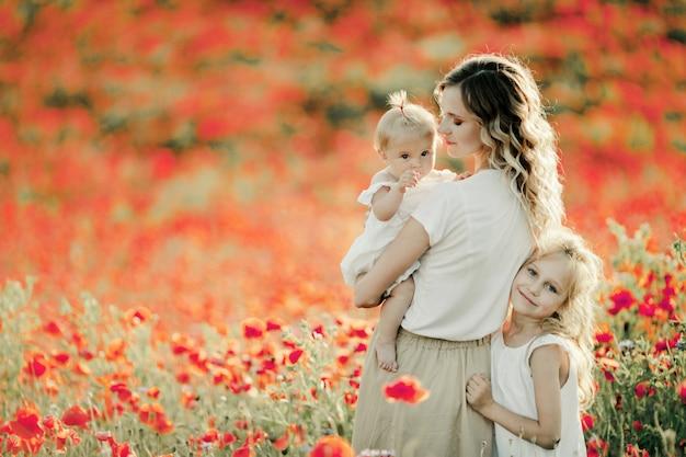 Mutter sieht ihr baby an, ältere tochter schmiegt sich an mutter auf dem mohnblumenfeld Kostenlose Fotos