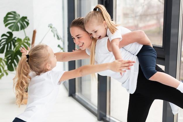 Mutter spielt mit töchtern zu hause beim training Kostenlose Fotos