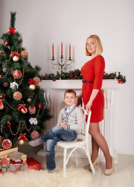 Mutter steht und jungen auf einem weißen stuhl sitzen Kostenlose Fotos