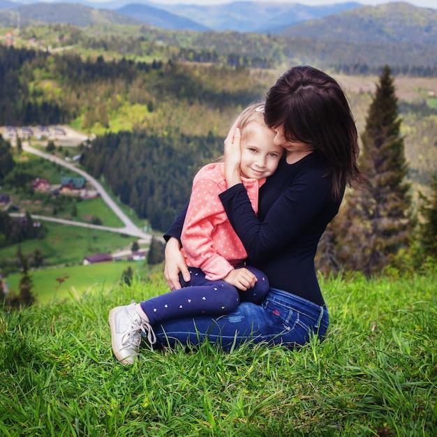 Mutter umarmt eine kleine tochter am gipfel des berges. Premium Fotos