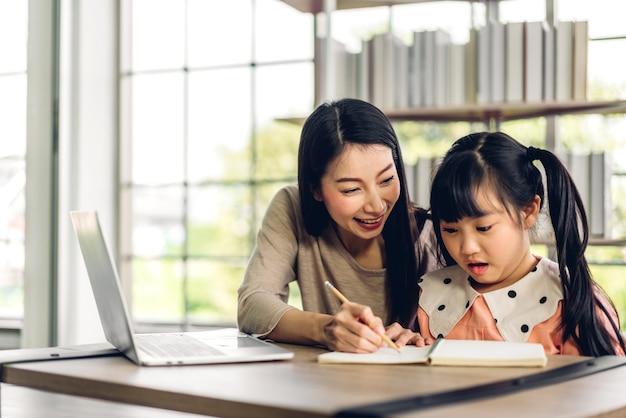 Mutter und asiatisches kind kleines mädchen lernen und betrachten laptop-computer machen hausaufgaben studieren wissen mit online-bildung e-learning-system Premium Fotos