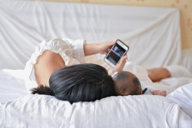 Mutter und baby, die im schlafzimmer spielen. mutter spielt handy auf dem bett. Premium Fotos