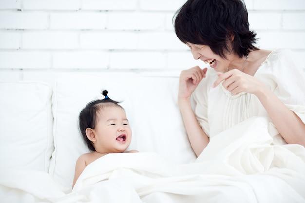 Mutter und baby lächeln sich auf einem weißen stuhl glücklich an. Premium Fotos