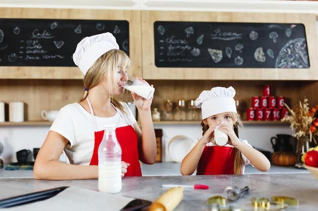 Mutter und charmante kleine tochter haben spaß beim trinken von milch am tisch in einer gemütlichen küche Kostenlose Fotos