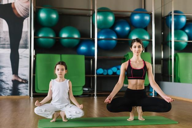 Mutter und frau, die zusammen yoga an der turnhalle tun Kostenlose Fotos