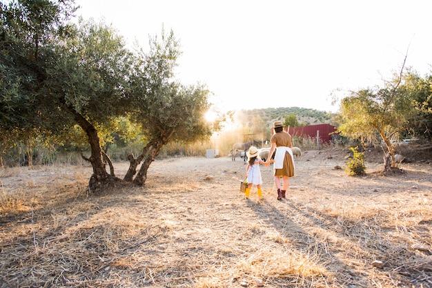 Mutter und ihre tochter, die auf dem gebiet gehen Kostenlose Fotos