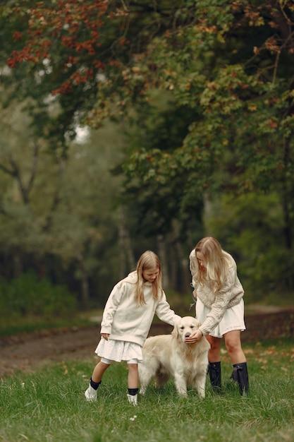 Mutter und ihre tochter spielen mit hund. familie im herbstpark. haustier-, haustier- und lebensstilkonzept Kostenlose Fotos
