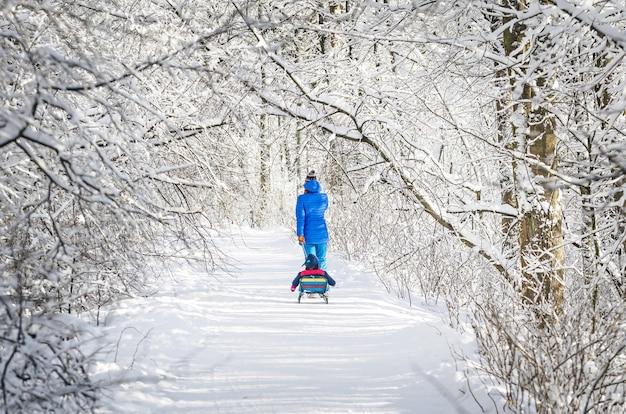 Mutter und kind auf einem schlitten auf einem winterweg in einem verschneiten wald. Premium Fotos