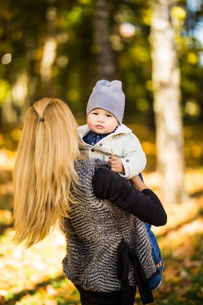 Mutter und kind gehen in den goldenen herbstpark Kostenlose Fotos