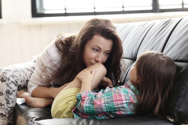 Mutter und kind haben spaß auf dem sofa Kostenlose Fotos