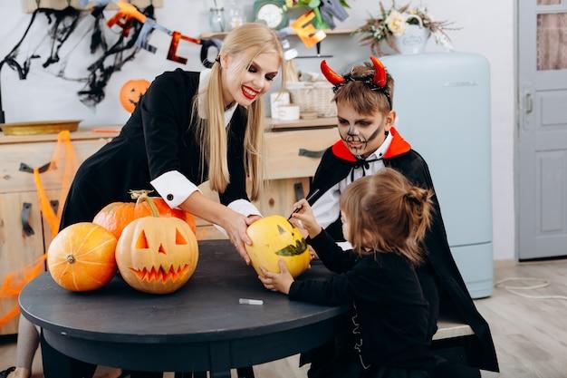 Mutter und kinder, die auf kürbis zeichnen, spielen und haben lustige zeit zu hause. halloween Premium Fotos