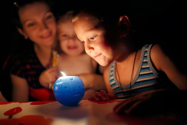 Mutter und kinder, die kerze betrachten Premium Fotos