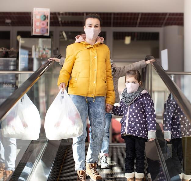 Mutter und kinder gehen mit masken während der quarantäne einen bagger in einem einkaufszentrum hinunter. Kostenlose Fotos