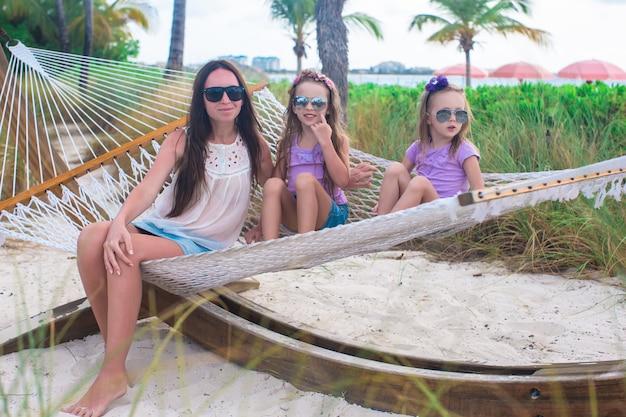 Mutter und kleine mädchen, die in der hängematte am tropischen erholungsort sich entspannen Premium Fotos