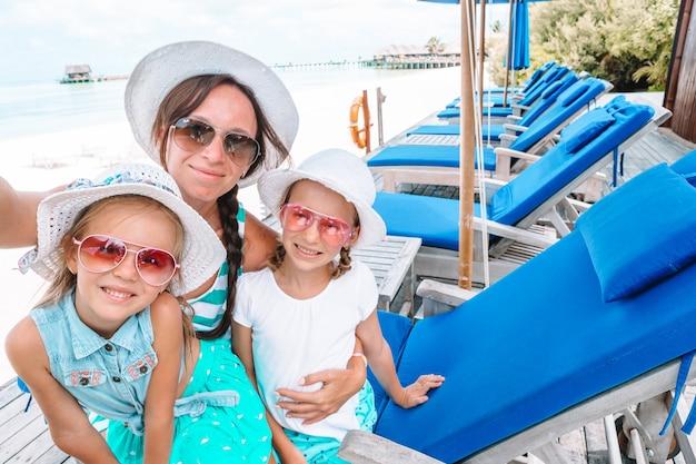 Mutter und kleine mädchen, die selfie am tropischen strand nehmen Premium Fotos
